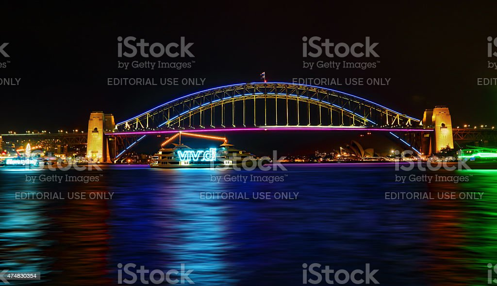Vivid Sydney-  boats cruise by Sydney Harbour Bridge in  colour stock photo