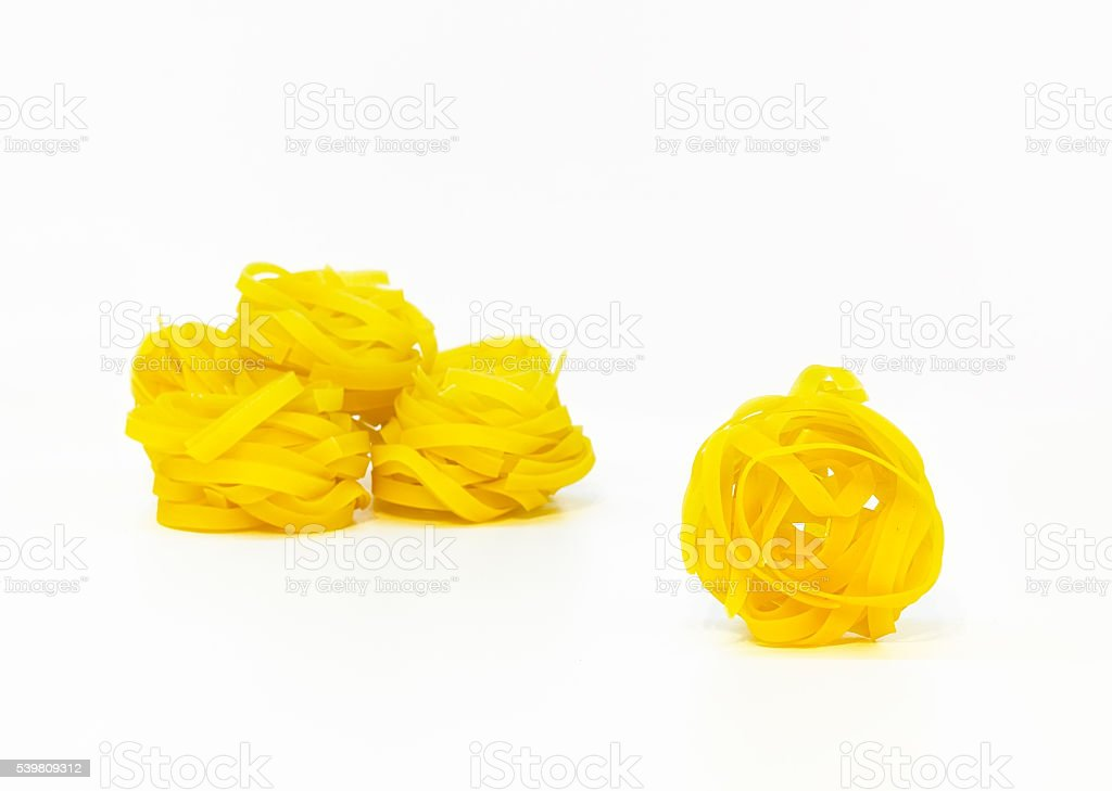 vivid yellow fettuccine pasta isolated on white background stock photo