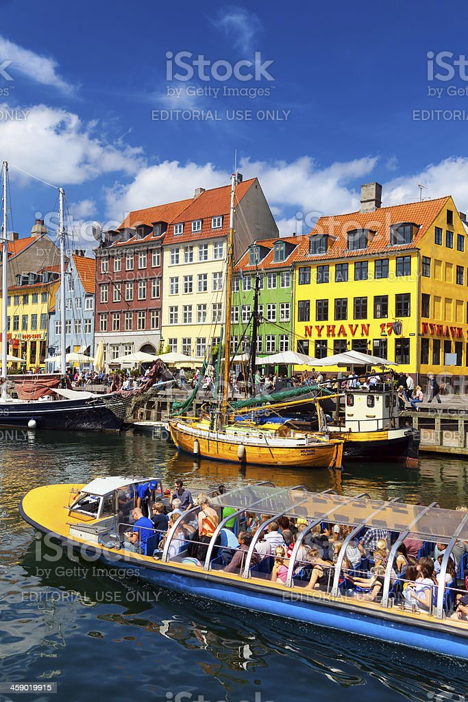 Vividly-coloured houses and a tour boat at Nyhaven, Copenhagen stock photo