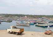Kovalam, India - October 19, 2013: A large number of boats crowd Vizhinjam fishing harbor at Kovalam as fishermen sell their catch on the beach in the state of Kerala. This is one of the many beaches at Kovalam.