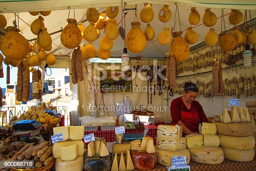 Vizzini, Sicily, Italy - April 25, 2014:  A vendor selling cheese and salami at an outdoor booth in Vizzini's annual ricotta festival. Vizzini is in the province of Catania.