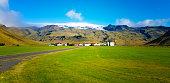 istock Vík í Mýrdal, Iceland: Farm Backdropped by Volcano/Icecap 1205423971