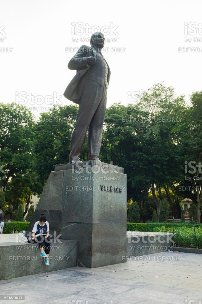 Hanoi, Vietnam - July 10, 2016: Vladimir Ilyich Lenin statue, with a student reading book by the statue, in Lenin park, Dien Bien Phu street stock photo