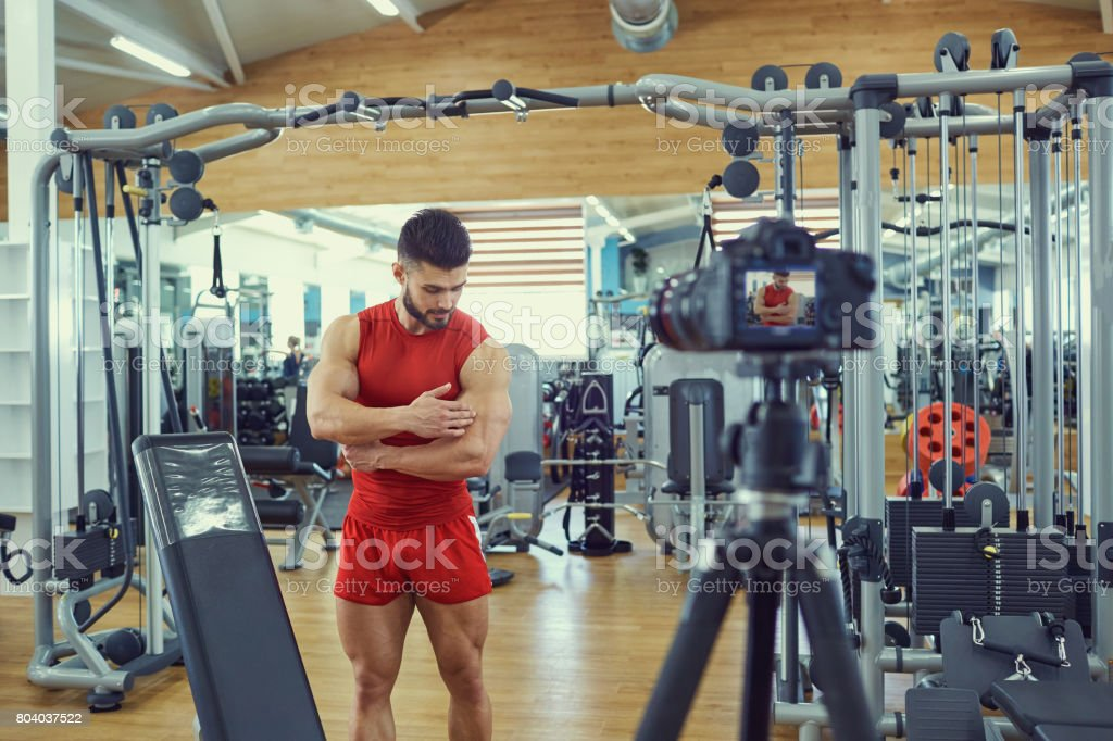 Vlogger athlete makes a video in the gym. stock photo