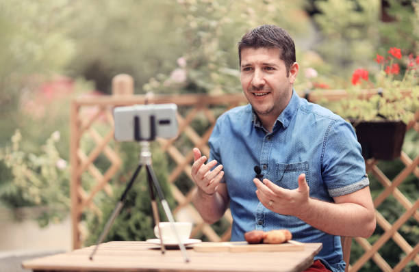 Vlogger man sitting on a table and making a vlog episode stock photo