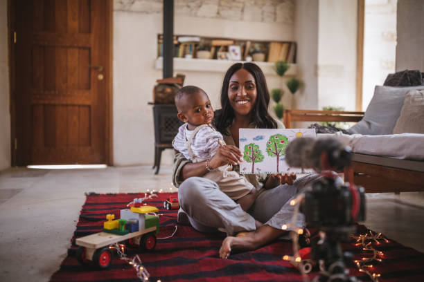 Vlogger mother with little son recording video for social media Social media influencer mother with little baby boy vlogging at home and showing kid's drawing wundervisuals stock pictures, royalty-free photos & images