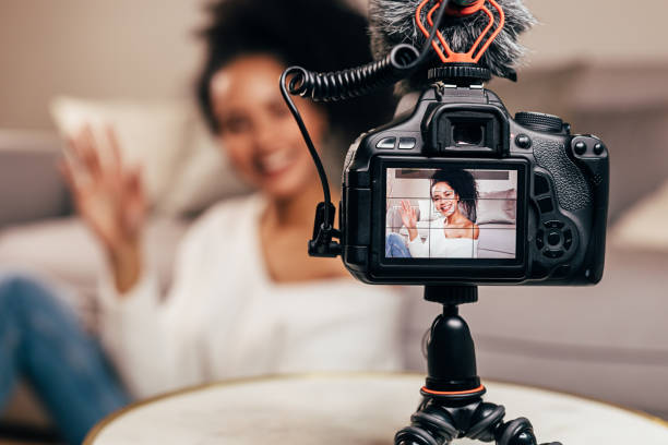 Vlogger recording content for her blog on a DSLR camera stock photo