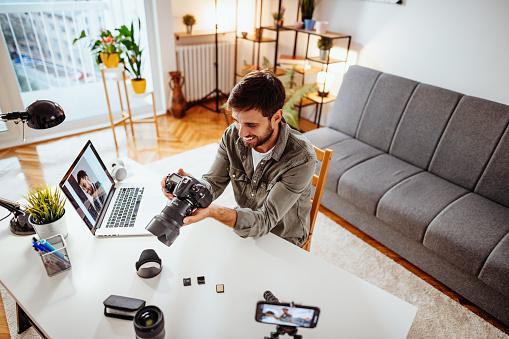 Young entrepreneur - marketing influencer testing camera for his vlog