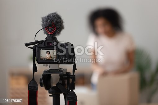 Vlogger using professional digital camera with microphone close up, recording parcel unboxing video for channel in social network, reviewing products, cardboard box with online store order
