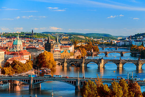 vltava river and charle bridge with red foliage - tsjechië stockfoto's en -beelden