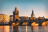 Panoramic highly detailed view from distance towards Vltava river and the famous Charles bridge in beautiful City of Prague, the capital of the Czech republic. The image is a long exposure with blurred water reflections and constant tourist crowds passing the iconic bridge sunlit by the setting Sun during afternoon on a clear day. Shot on Canon EOS R system with premium lens for highest quality.