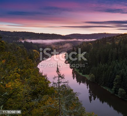 Vltava river from vantage point with fog and trees at sunrise, blue hour