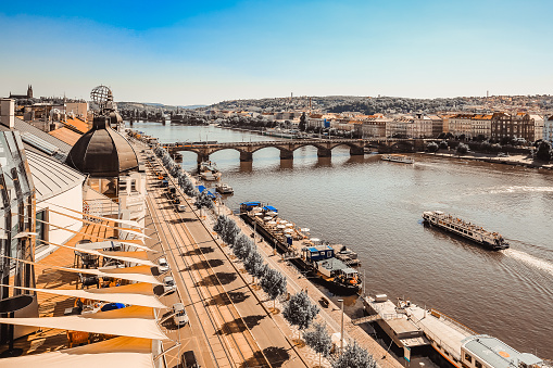 Panoramic view of Prague Old Town, Czech Republic. Palacky Bridge over Vltava river. Historical buildings on waterfront. Cruise motor ships on water. Travel destination. Sepia toned