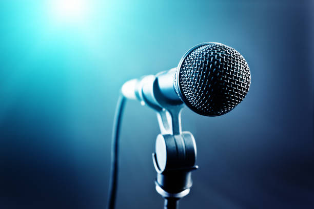 Vocal microphone in front of blue-toned stage lights stock photo