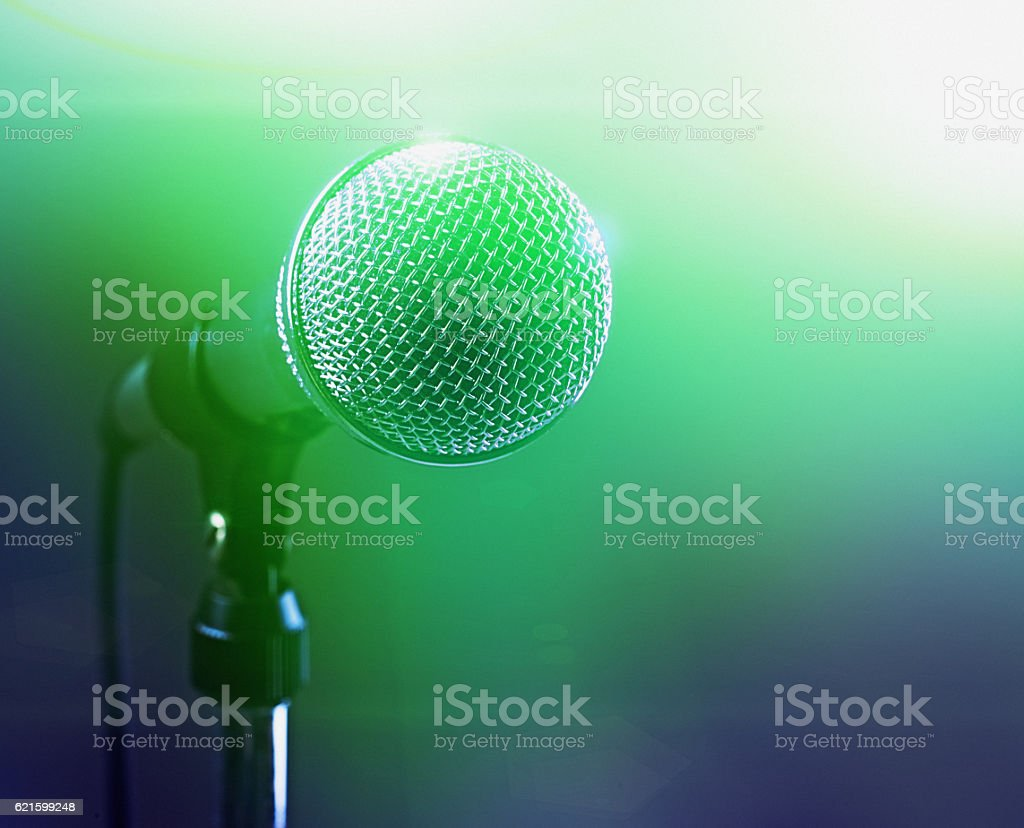 Vocal microphone in smoky green stage lighting stock photo