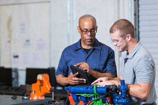 An African American man instructing a Caucasian student on how to repair a diesel engine. He is teaching a class in a vocational school, for learning the auto mechanic trade. They are standing by an engine block which is color-coded for the classroom.  The instructor is holding a digital tablet.
