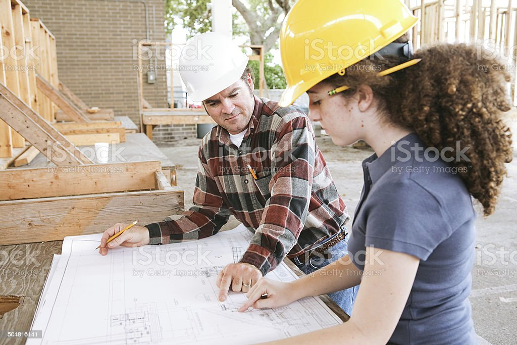 Vocational Training - Blueprints Vocational education student learning to read construction blueprints. Adult Stock Photo
