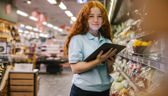 Happy woman working in a supermarket. Caucasian female grocery store employee with a digital tablet.