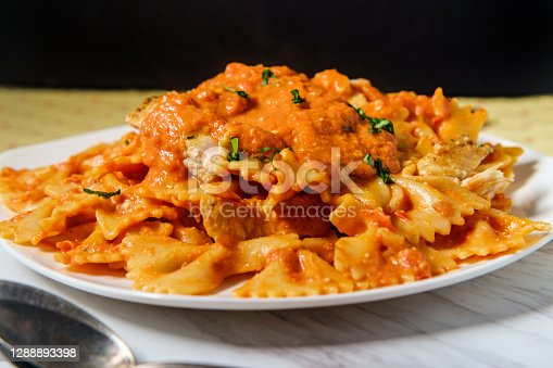 Farfalle bow tie pasta in creamy vodka tomato sauce with grilled chicken and green peas