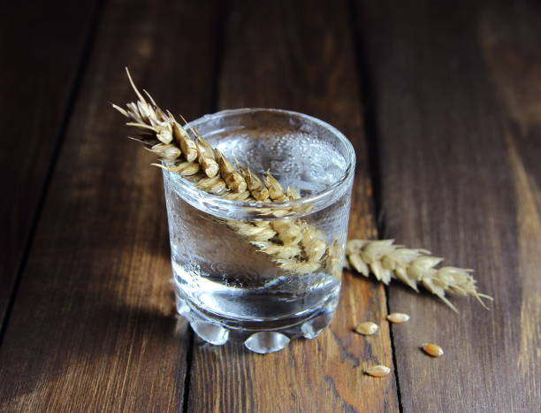 vodka in a glass with ears vodka in a glass with ears of wheat on wooden background vodka stock pictures, royalty-free photos & images