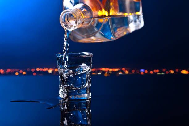 vodka in bar on a black  background vodka in bar on a black reflective background vodka stock pictures, royalty-free photos & images