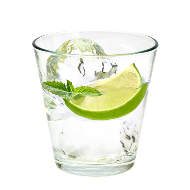 Vodka in rocks glass isolated on white background Vodka with ice and lime wedge isolated on white background tequila shot stock pictures, royalty-free photos & images