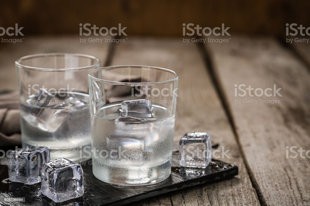 Vodka in shot glasses on rustic wood background stock photo