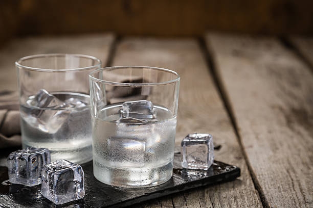 Vodka in shot glasses on rustic wood background - Photo