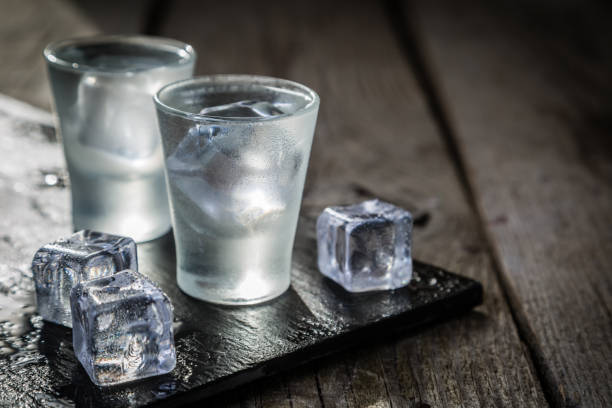 Vodka in shot glasses on rustic wood background