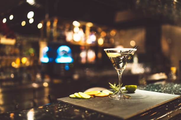 Vodka Martini cocktail on a counter in a bar Glass of martini on a grnished surface with lemon slices and rosemary. Black bakground. Glas garnished with sugar on the edge. martini stock pictures, royalty-free photos & images