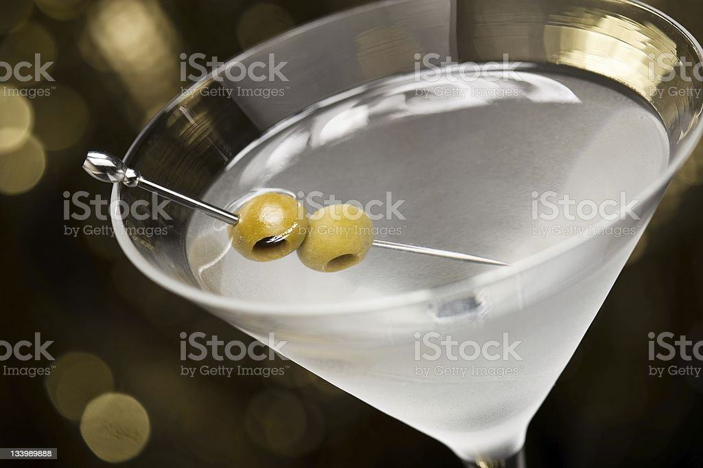 Vodka Martini with olive garnish in front of a gold stock photo