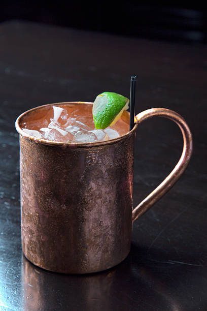 Vodka Moscow Mule Cocktail with Lime Copper Mug A cold icy Moscow Mule cocktail with vodka, ginger beer and lime in a traditional frosty copper mug mule stock pictures, royalty-free photos & images