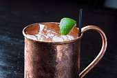 A cold icy Moscow Mule cocktail with vodka, ginger beer and lime in a traditional frosty copper mug