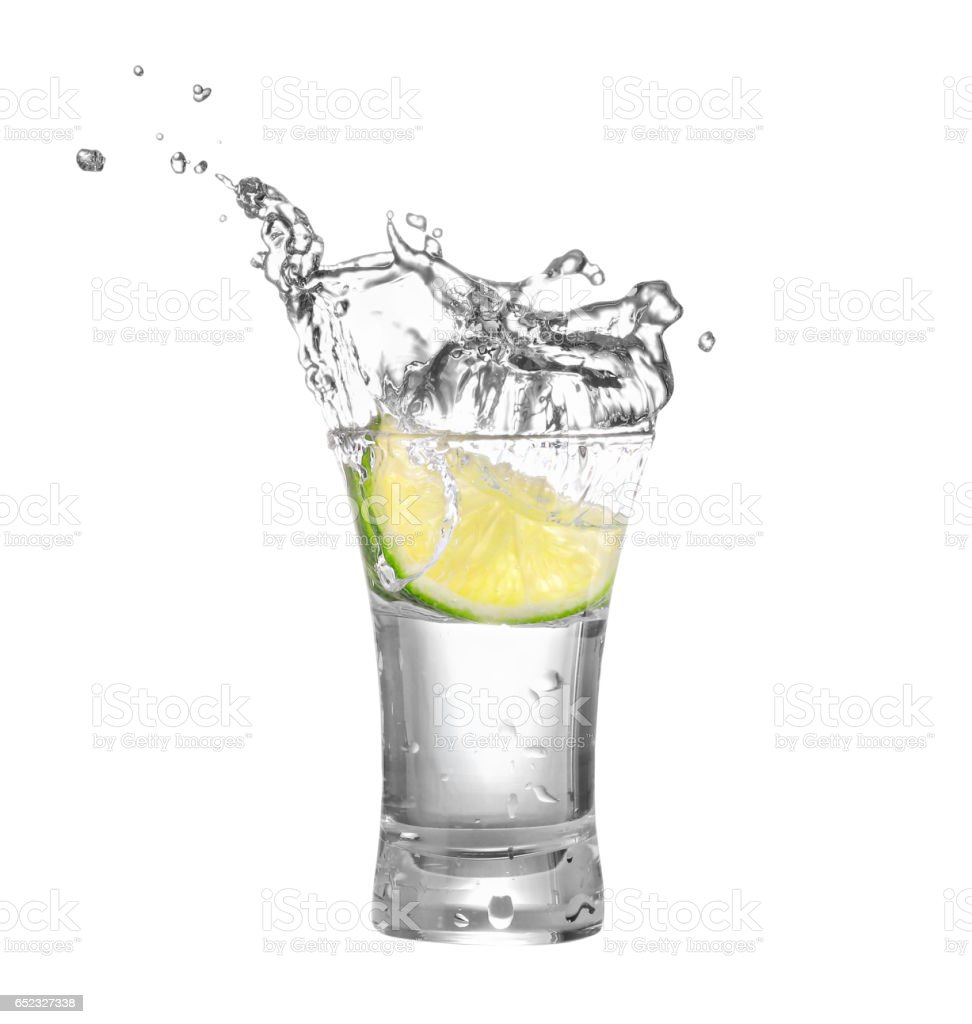 vodka or tequila in glass with lime slice stock photo