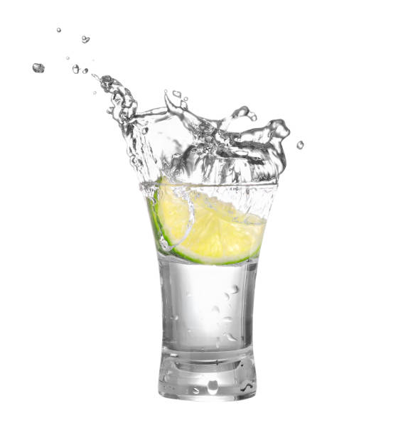 vodka or tequila in glass with lime slice shot of vodka or tequila with lime slice and splash isolated on white background. Lime is falling in the alcohol drink. Splash of vodka  from the falling piece of lime. Clipping path tequila shot stock pictures, royalty-free photos & images