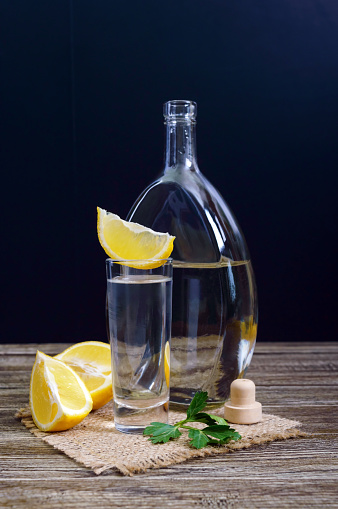 498688230 istock photo Vodka or tequila in shot glasses and in the bottle with lemon sliсe on rustic wooden background. Traditional strong drink. Close-up. Vertical view 938404222