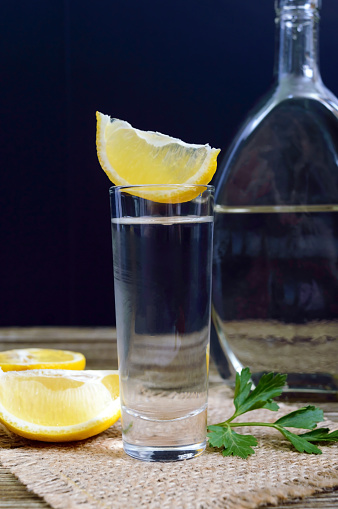 498688230 istock photo Vodka or tequila in shot glasses and in the bottle with lemon sliсe on rustic wooden background. Traditional strong drink. Close-up. Vertical view 938404224