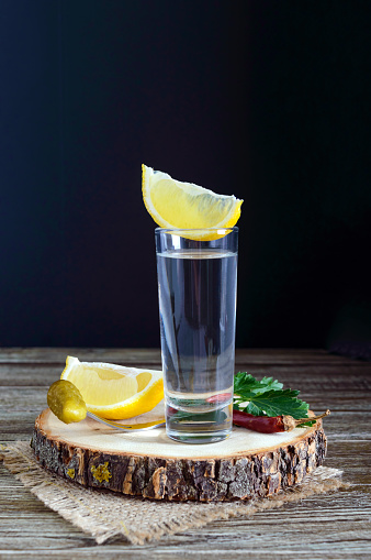 498688230 istock photo Vodka or tequila in shot glasses and in the bottle with lemon sliсe on rustic wooden background. Traditional strong drink. Close-up. Vertical view 938404230