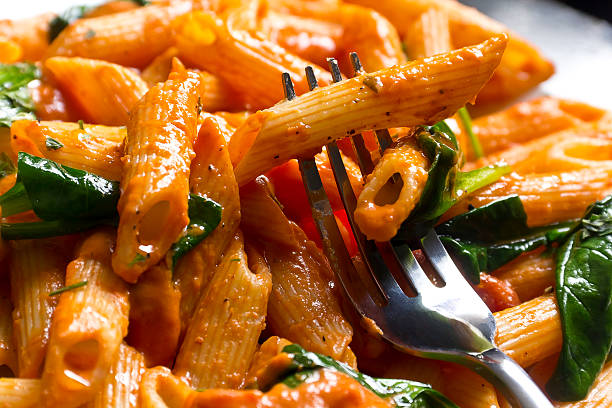 Penne Alla Vodka Penne pasta in creamy vodka tomato sauce with sauteed baby spinach leaves vodka stock pictures, royalty-free photos & images