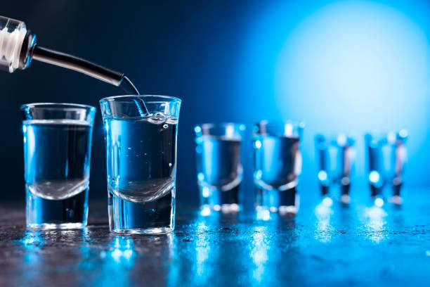 Vodka poured into a glass lit with blue backlight. Vodka poured into a glass lit with blue backlight. Copy space. vodka stock pictures, royalty-free photos & images