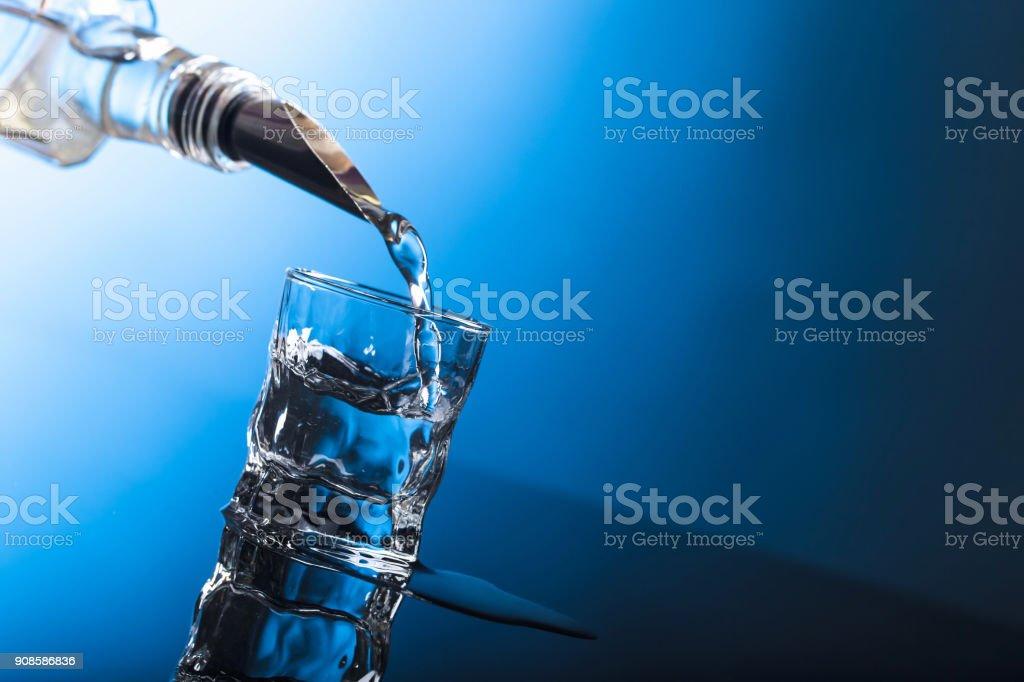 Vodka coulent de la bouteille en verre dans un bar. - Photo
