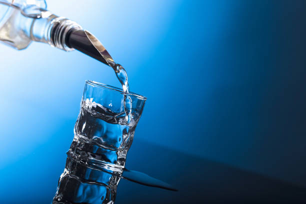 Vodka pouring from the bottle into  glass in a bar. Russian vodka pouring from the bottle into  glass in a bar. Copy space. vodka stock pictures, royalty-free photos & images