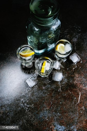 578566044 istock photo Vodka. Shots, glasses with vodka and lemon with ice .Dark stone background. Vertical image. 1140193411