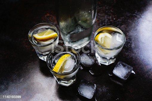 578566044 istock photo Vodka. Shots, glasses with vodka and lemon with ice .Dark stone background. 1140193399