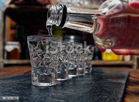 Crystal shot glasses of vodka standing in a row. Pouring vodka from a bottle to the shot glass