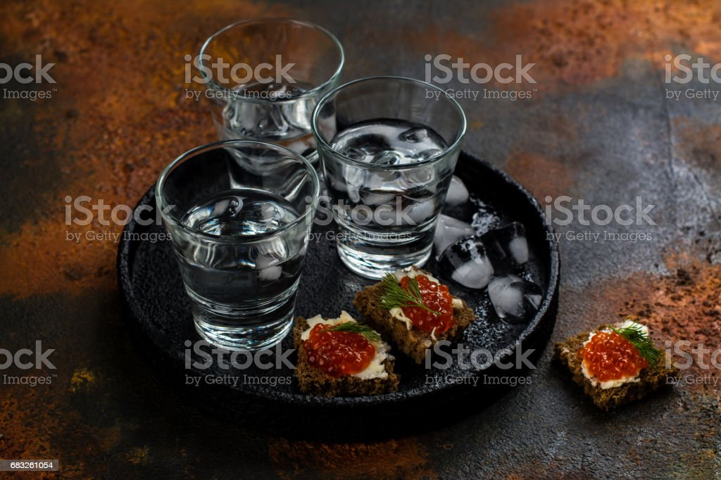 Vodka shots with ice and small snack sandwiches royalty-free stock photo