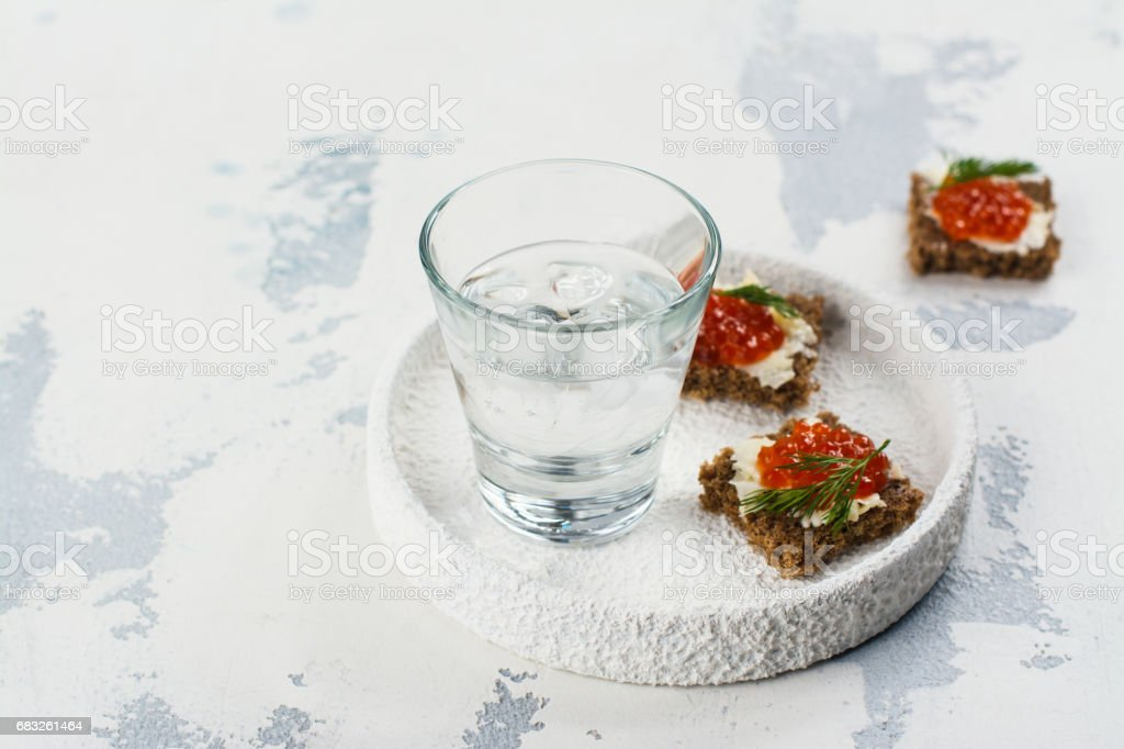 Vodka shots with ice and small snack sandwiches foto de stock royalty-free