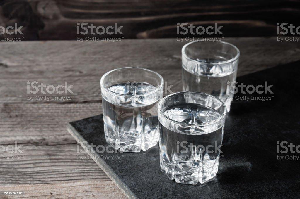 Wodka-Shots mit Eiswürfeln auf schwarzem Stein, – Foto
