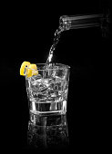Vodka pouring into a glass on a reflective black surface. Image is isolated on black.