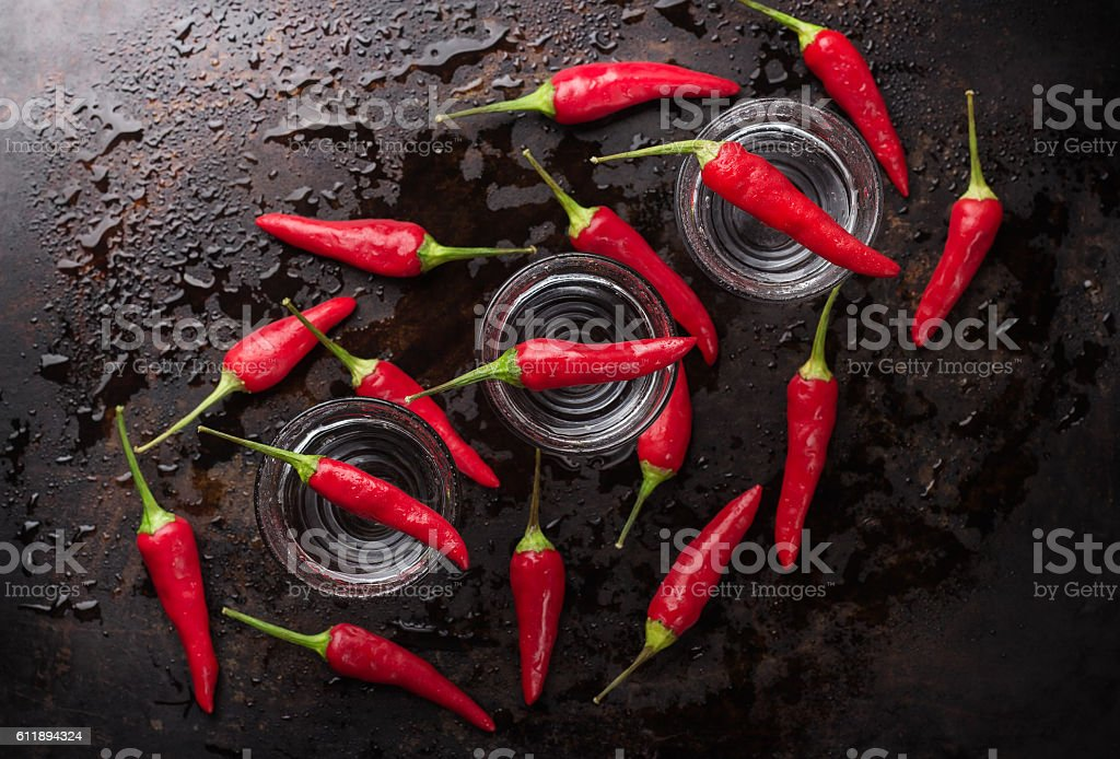Vodka with chili peppers on rusty grunge table stock photo